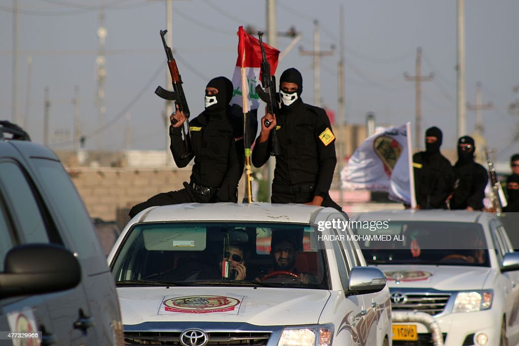 Fighters of the Ansar Allah alAwfiya Shiite group parade with their weapons on June 16 2015 in the southern Iraqi city of Basra during celebrations...
