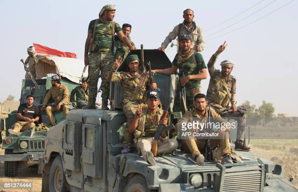 Fighters of the Hashed alShaabi paramilitaries flash the victory gesutre while riding on top of humvees as they advance towards the northern Iraqi...