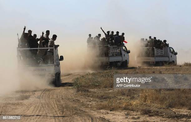Fighters of the Hashed alShaabi paramilitaries flash the victory gesture while riding in the back of trucks advancing towards the northern Iraqi town...