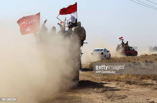 Fighters of the Hashed alShaabi paramilitaries flash the victory gesture while riding in the back of a truck advancing towards the northern Iraqi...