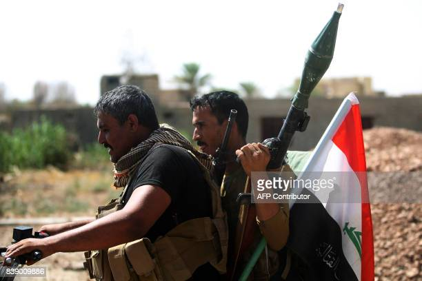 Fighters of the Hashed alShaabi ride in a motorcycle as one carries a rocketpropelled grenade launcher and an Iraqi flag during their advance in the...
