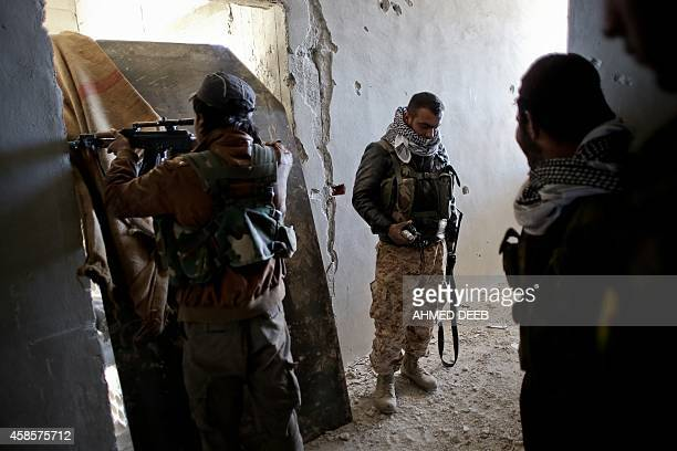 Fighters of the Syrian Kurdish People's Protection Units hold a position during fighting against Islamic State group on November 7 2014 in the Syrian...