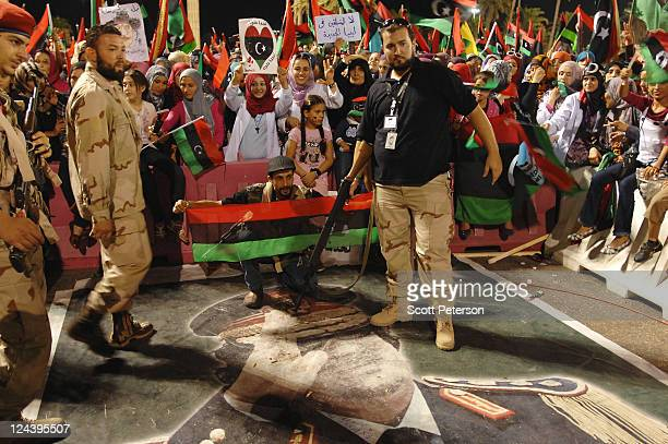 Fighters step on a poster of toppled dictator Col Muammar Gaddafi as thousands of Libyans rally for their revolution in Green Square now renamed...