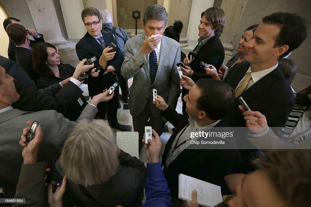Fighting a cold, Sen. <a gi-track='captionPersonalityLinkClicked' href=/galleries/search?phrase=Joe+Manchin&family=editorial&specificpeople=568465 ng-click='$event.stopPropagation()'>Joe Manchin</a> (D-WV) (C) talks with reporters at the U.S. Capitol October 14, 2013 in Washington, DC. President Barack Obama postponed a meeting with Congressional leaders after the possiblity of a legislative solution to the partial federal government shutdown and the looming debt ceiling.