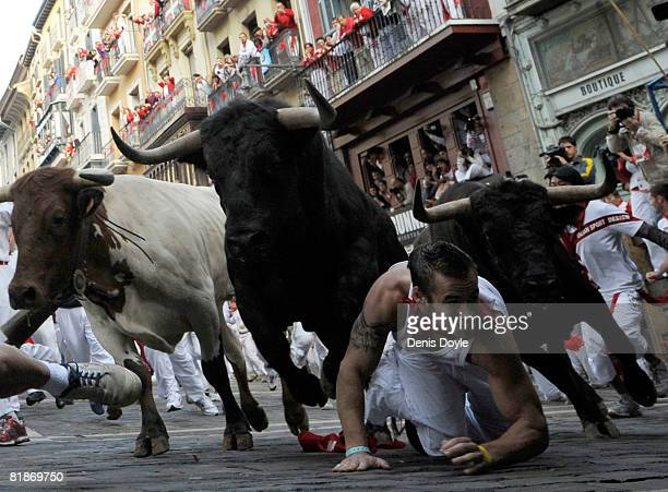 A fighting bull leaps over a fallen runner at the Mercaderes curve during the third San Fermin running of the bulls on July 9 2008 in Pamplona Spain...