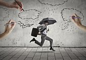 Business man is fighting for surviving with an umbrella in his hand