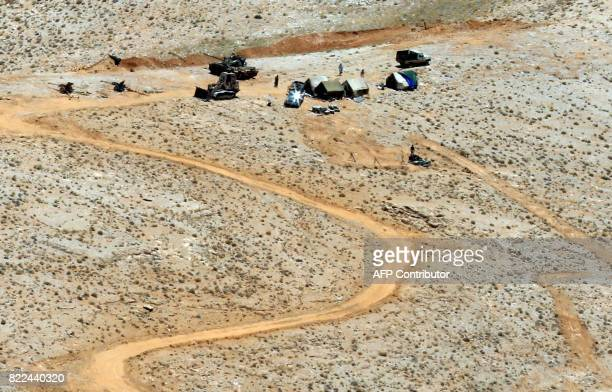 Fighting vehicles and weapons are seen in a mountainous area around the Lebanese border town of Arsal on July 25 2017 during a press tour organised...