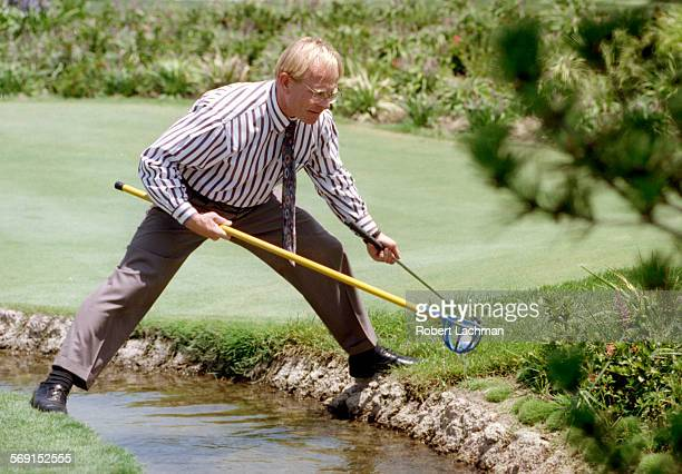 FIGreens/StreamRDL John Greisen of Huntington Beach uses a special scooper to retreive his golf ball as he straddles a stream which surrounds the...