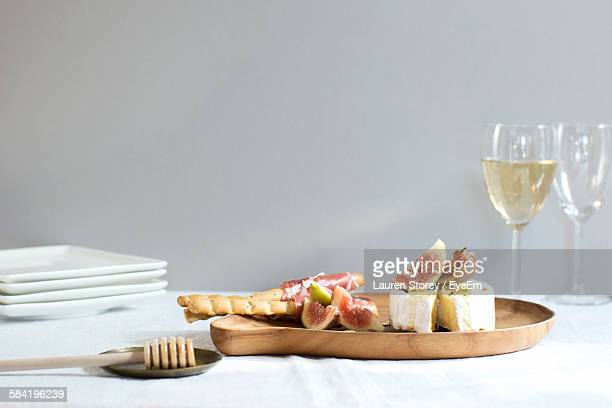 Figs And Cheese In Plate With Wineglass On Table