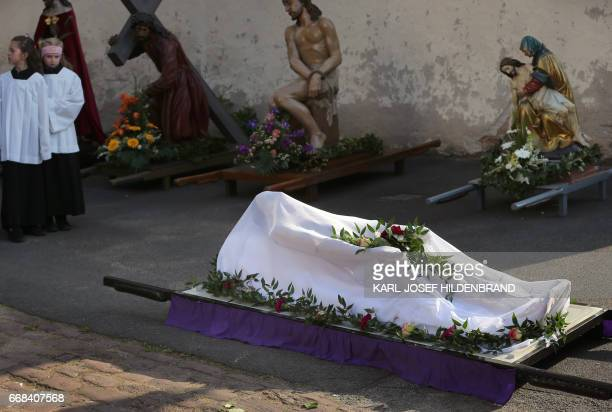 A figure of Jesyus Christ being laid on a bier is covered ahead a Good Friday procession in Lohr am Main southern Germany on April 14 2017 / AFP...