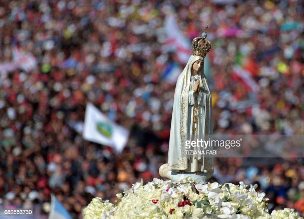 A figure representing 'Our Lady of Fatima' is carried among the faithful at Fatima's Sanctuary central Portugal on May 13 2017 Two of the three child...