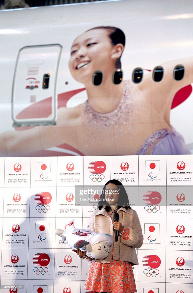 Figure skater <a gi-track='captionPersonalityLinkClicked' href=/galleries/search?phrase=Mao+Asada&family=editorial&specificpeople=247229 ng-click='$event.stopPropagation()'>Mao Asada</a> poses for photographs with her picture wrapping airplane at a hangar of Japan Airlines on December 23, 2013 in Tokyo, Japan.