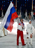 Figure skater Maxim Trankov of Russia enters with the flag during the 2014 Sochi Winter Olympics Closing Ceremony at Fisht Olympic Stadium on...