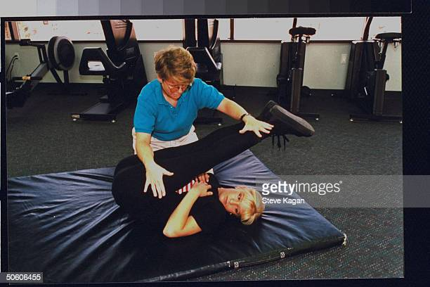 Figure skater Nicole Bobek stretching out legs w physical therapist Heather Graham while lying on mat at Optimax Human Performance Institute Bobek...