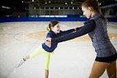 Figure skater positioning students arms