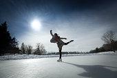 Figure Skater Skating Against Sun on Winter Pond Ice Rink