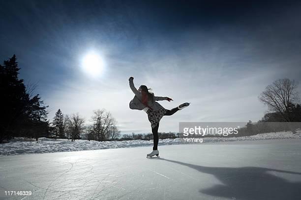 Eiskunstläuferin Skating gegen Sonne auf Winter Pond Ice Rink
