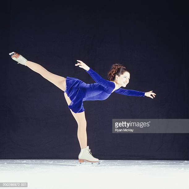 Figure skater skating on ice rink, side view