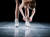 Figure skater standing on ice adjusting skate