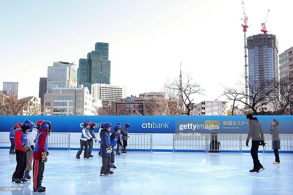 Figure skaters Shizuka Arakawa (R), the 2006 Turin Winter Olympics figure skating gold medalist, and Evan Lysacek (2nd R) of the United States, the 2010 Vancouver Winter Olympics figure skating gold medalist, teach ice skating to children after the opening ceremony for the Citi Ice Rink at Tokyo Midtown on January 6, 2011 in Tokyo, Japan. The outdoor ice skating rink will open between January 7 and February 28.