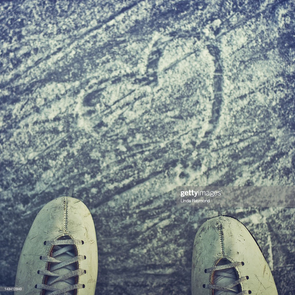 Figure skates and shape of heart drawn on ice