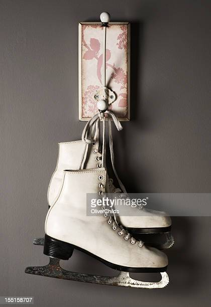 Figure skates hanging from a coat peg.