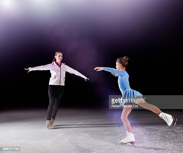 Figure skating coach and pupil practicing routine