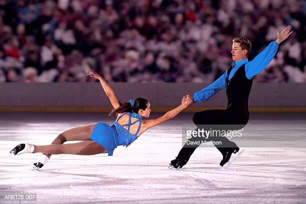 Figure skating pair performing in front of crowd (Digital Composite)