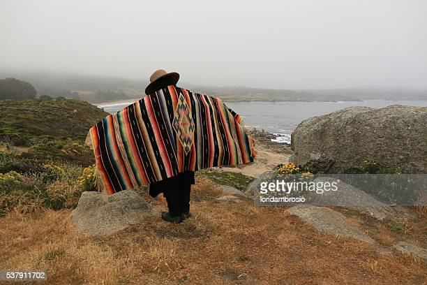 Figure wearing an antique serape and a straw hat on the rocks above the Pacific Ocean