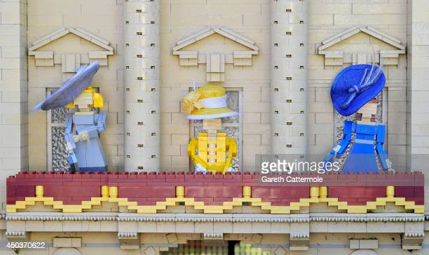 LEGO figures of Camilla Duchess of Cornwall Queen Elizabeth II Catherine Duchess of Cambridge stand outside a LEGO Buckingham Palace wearing designer...