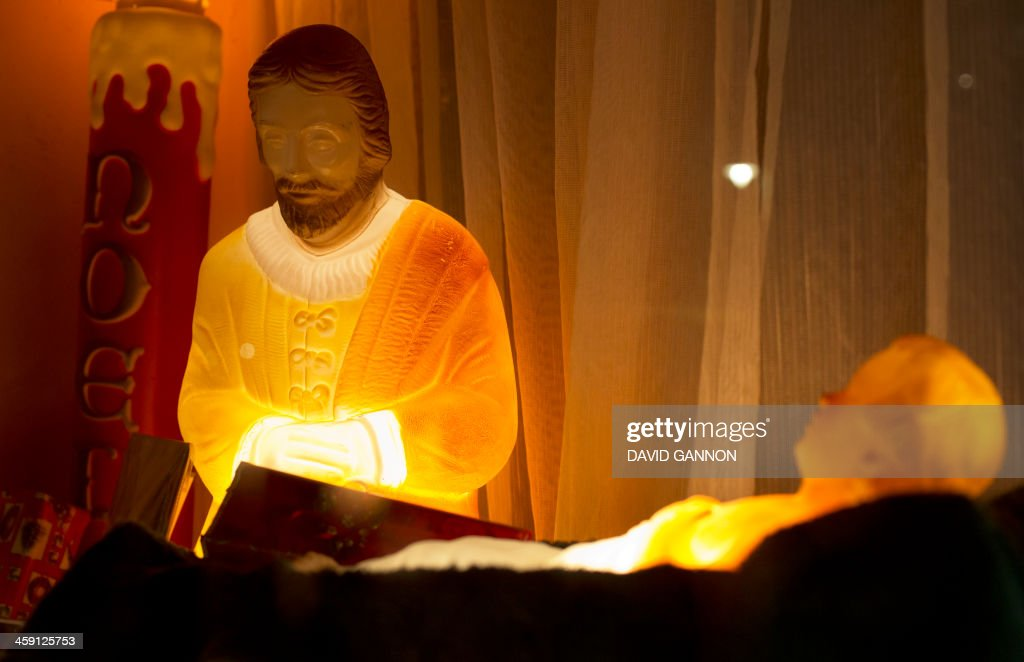 Figures of the baby Jesus (R) and Joseph are on display in the window of a pet shop on December 23, 2013 in Berlin.