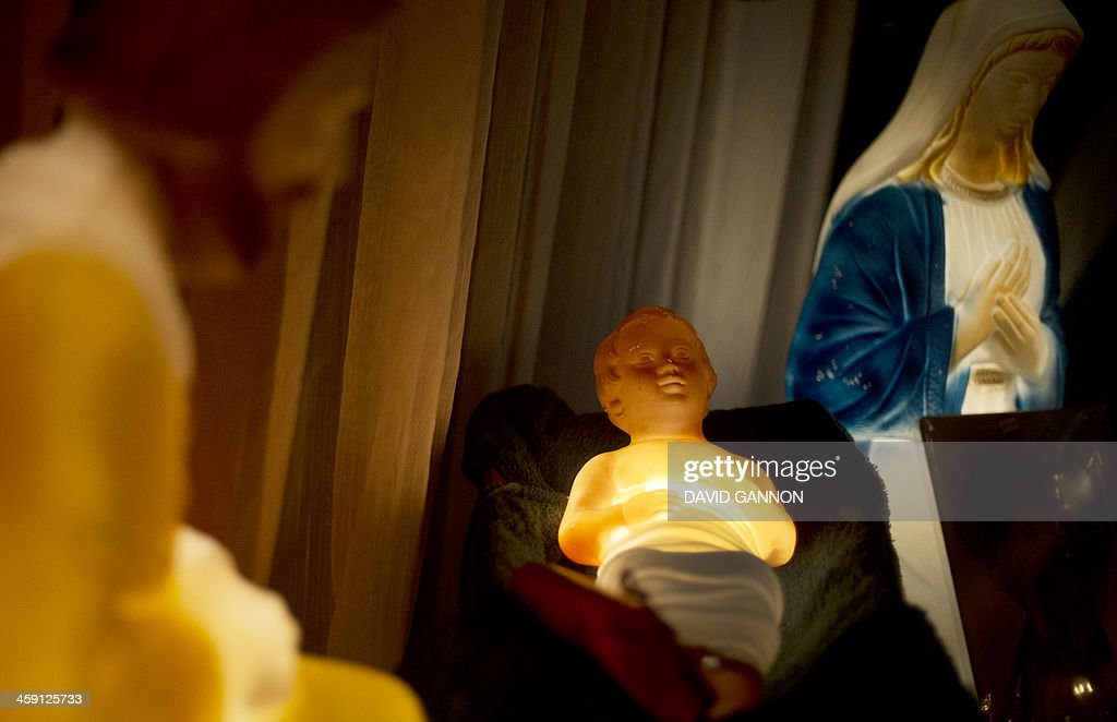 Figures of the baby Jesus (C), Mary (R) and Joseph are on display in the window of a pet shop on December 23, 2013 in Berlin.