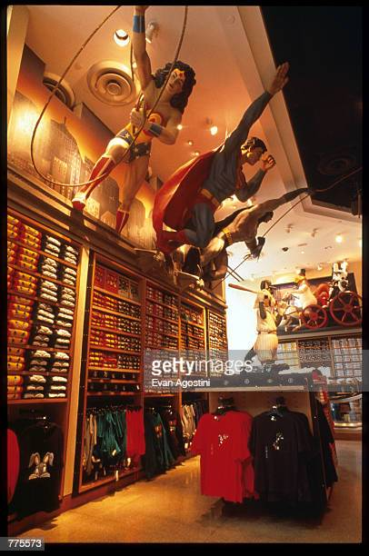 Figures of Wonder Woman Superman and Batman hang from a shelf at the Warner Bros Studio store October 23 1996 in New York City The store originally a...