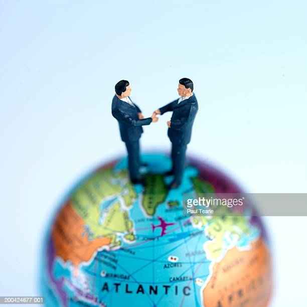 Figurine businessmen shaking hands on top of globe, close up