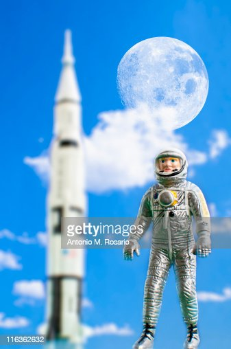 Figurine of astronaut with rocket in background : Stock Photo