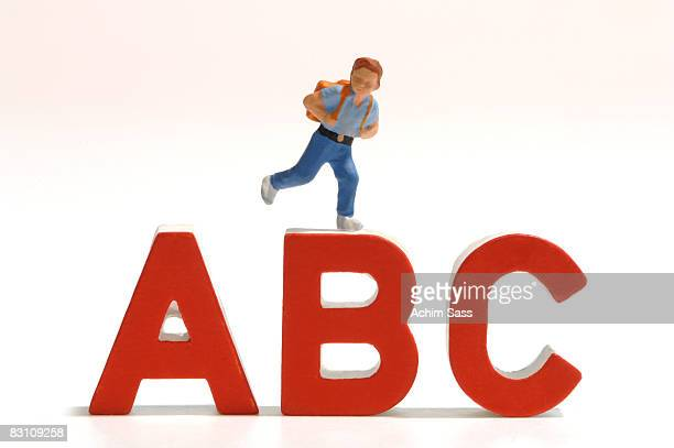 Figurine of schoolboy on letter ABC, close-up