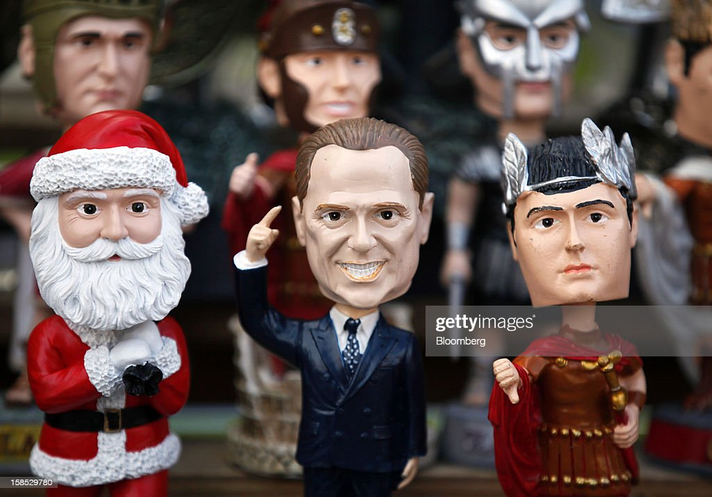 A figurine of Silvio Berlusconi, Italy's former prime minister, center, sits on display with other tourist souvenirs including Santa Clause and Roman soldiers on a stall in Rome, Italy, on Tuesday, Dec. 18, 2012. Italian Prime Minister Mario Monti, who is under pressure from euro-area and business leaders to enter the Italian election campaign, plans to quit once parliament passes his budget this week. Photographer: Alessia Pierdomenico/Bloomberg via Getty Images