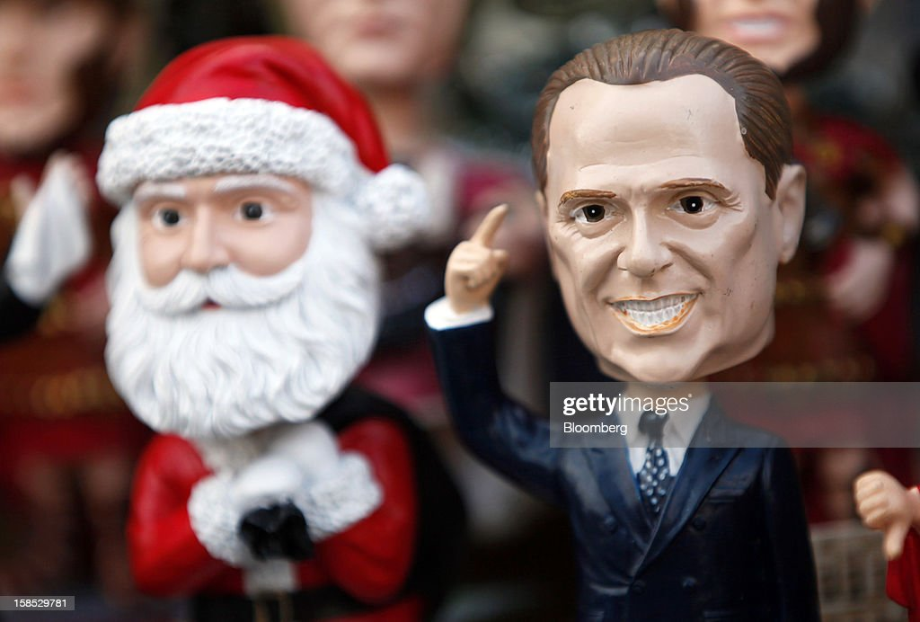 A figurine of Silvio Berlusconi, Italy's former prime minister, right, sits on display beside a figurine of Santa Clause with other tourist souvenirs on a stall in Rome, Italy, on Tuesday, Dec. 18, 2012. Italian Prime Minister Mario Monti, who is under pressure from euro-area and business leaders to enter the Italian election campaign, plans to quit once parliament passes his budget this week. Photographer: Alessia Pierdomenico/Bloomberg via Getty Images
