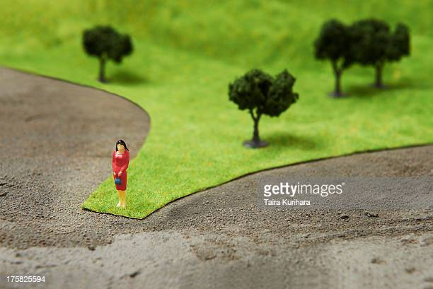 Figurine on pretend grass with trees