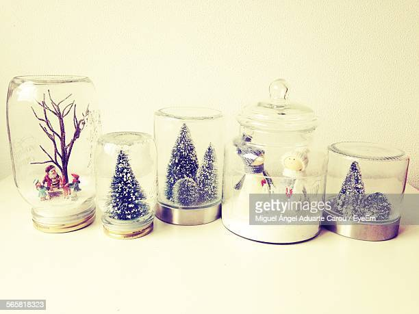 Figurines And Christmas Trees In Glass Container