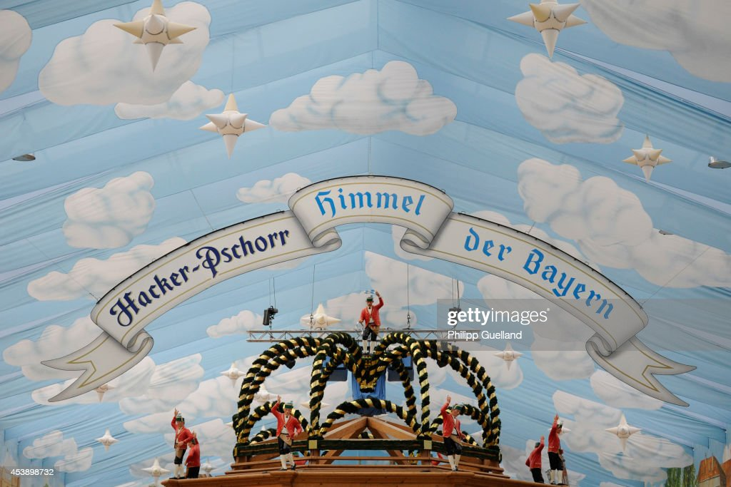 Figurines are seen below the slogan 'Heaven of Bavarians' (Himmel der Bayern) in the Hacker Pschorr brewery's tent four weeks ahead of Oktoberfest on August 21, 2014 in Munich, Germany. Munich Oktoberfest, which opens to the public on September 20, draws millions of visitors and is the biggest beer fest in the world. Photo by Philipp Guelland/Getty Images)