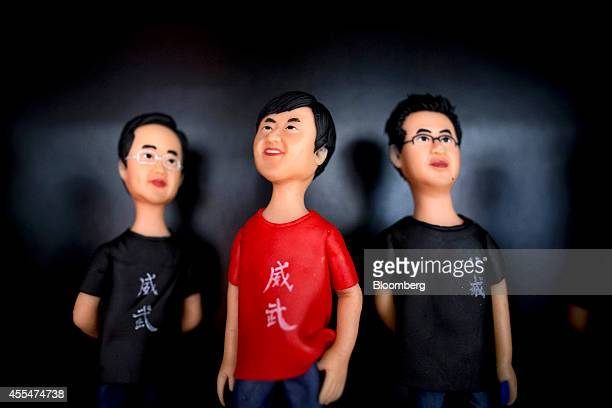 Figurines in the likeness of Lin Bun president of Xiaomi Corp left Lei Jun chief executive officer center and Zhou Guangping vice president stand on...