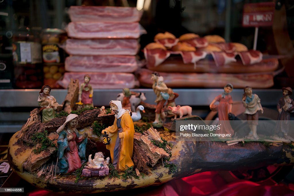 Figurines of a traditional Belen stand on top of a Spanish Ham seen in a window display of El Museo del Jamon 'Ham Musseum' shop in Gran Via, five days before Christmas Day on December 20, 2011 in Madrid, Spain. This year businesses are starting sales and discounts prior to Christmas Day to boost sales during the current economic crisis.