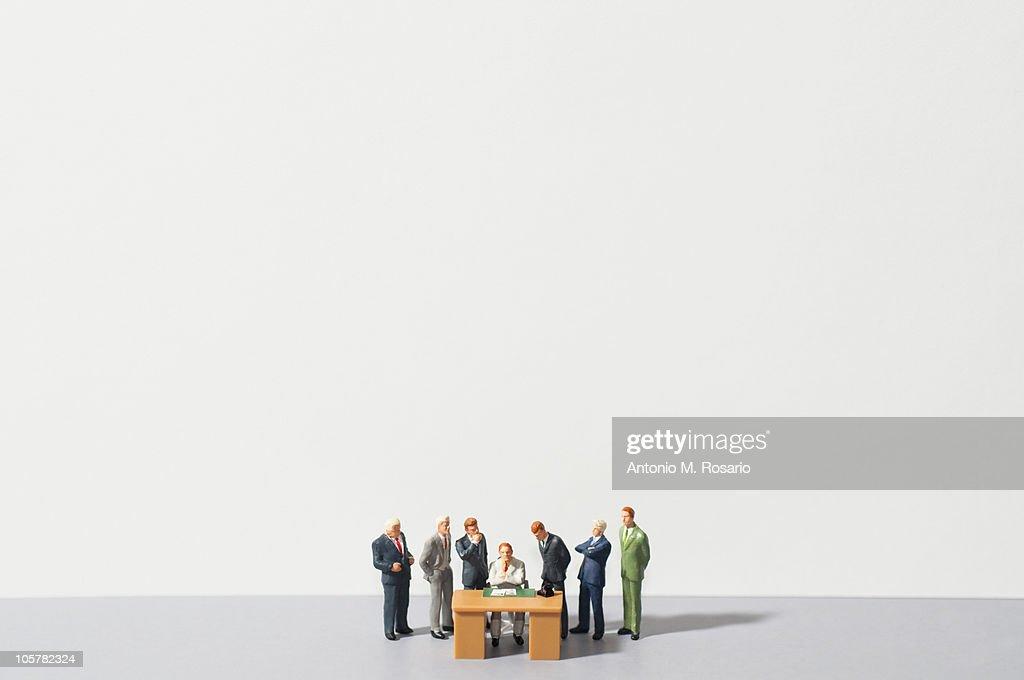 Figurines of people standing around desk