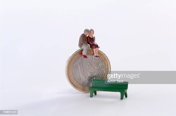Figurines sitting on coin, bench aside
