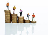 Figurines standing on stack of coins