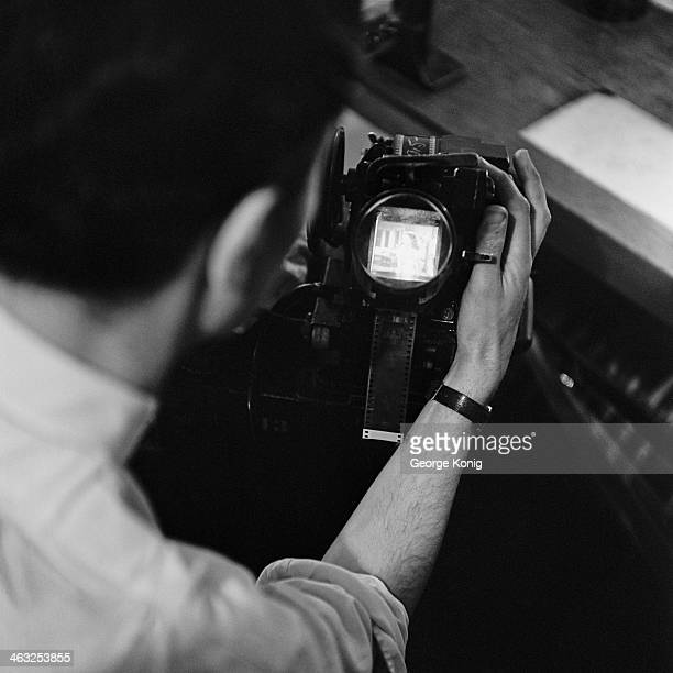Fiilm editor cutter Alan Jaggs using a moviola to review footage from the previous day's shooting on Brian Desmond Hurst's 'Hungry Hill' at Denham...