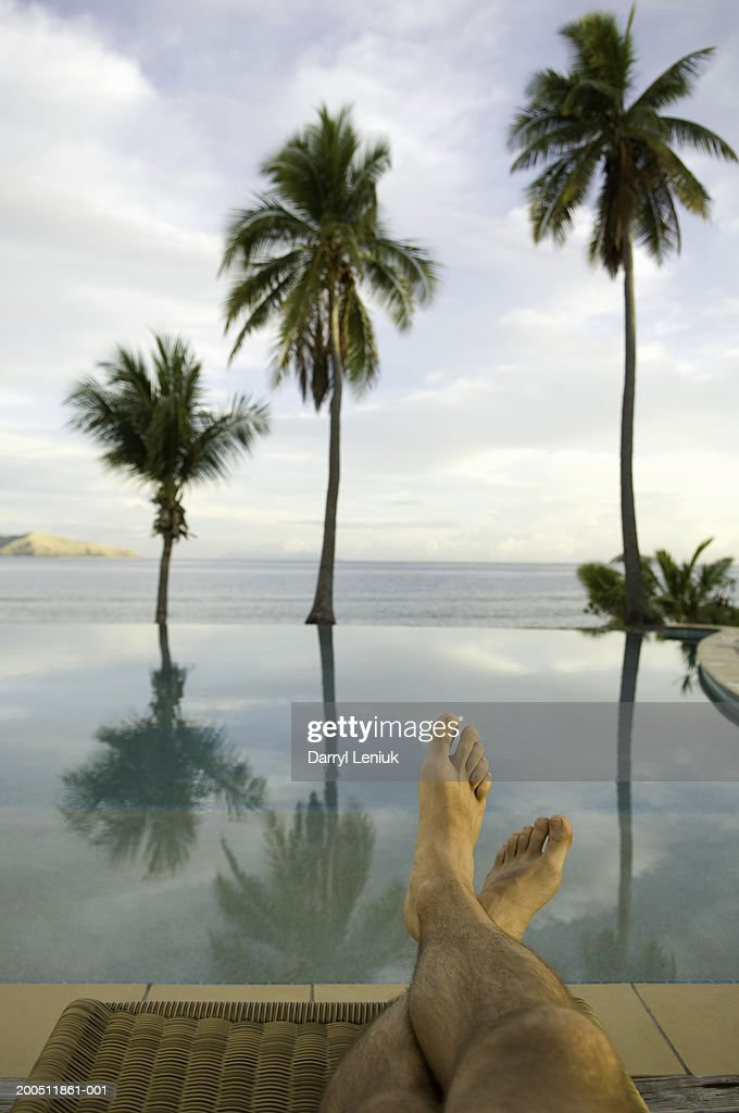 Fiji, man sitting on lounge chair beside infinity pool, low section : Stock Photo