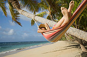 Fiji, Namenalala Island, young woman lying in hammock on beach