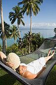 Fiji, Vanua Levu Island, young woman lying in hammock, elevated view